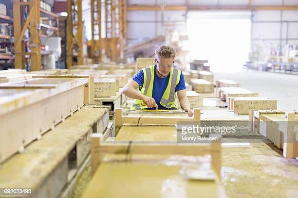 apprentice moulding stone in architectural stone factory - baumaterial stock-fotos und bilder