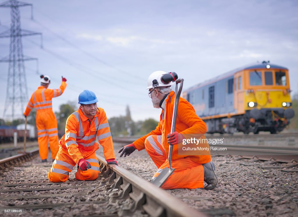 Apprentice railway worker instructed by engineer on railway : Stock Photo