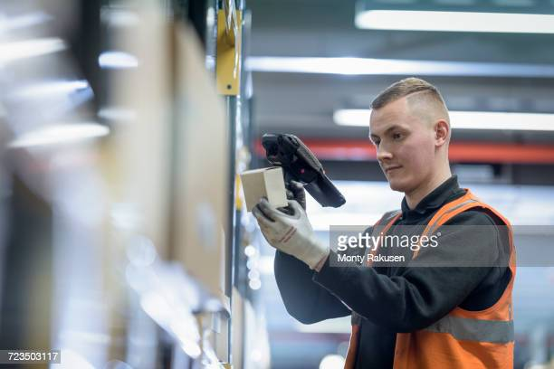 Apprentice scanning parts numbers in parts store in car factory
