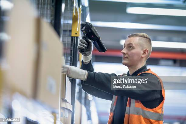apprentice scanning parts numbers in parts store in car factory - monty rakusen stock pictures, royalty-free photos & images