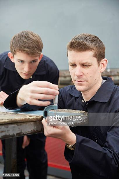 Apprentice watching engineer measuring metal with micrometer