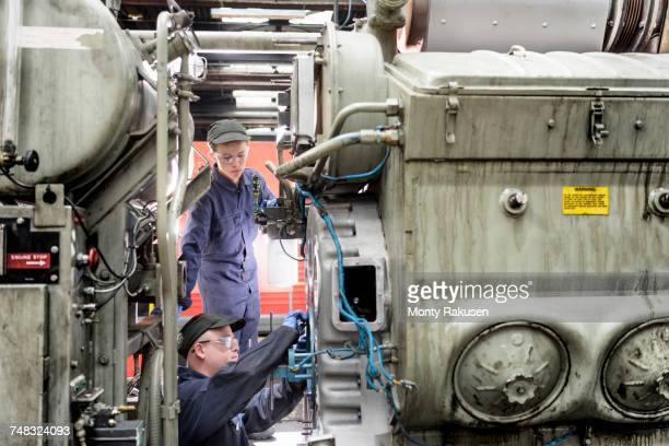 Apprentice watching engineer working on locomotive engine in train works