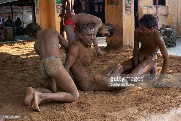 CONTENT] Apprentices applying loose mud on their senior's body at an akhara after a wrestling bout in Varanasi India