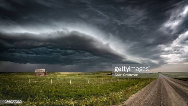 approaching thunderstorm with abandoned schoolhouse - prairie stock pictures, royalty-free photos & images