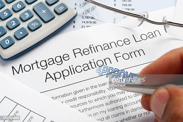 approved mortgage refinance application form with pen, calculato - mortgage document stock pictures, royalty-free photos & images