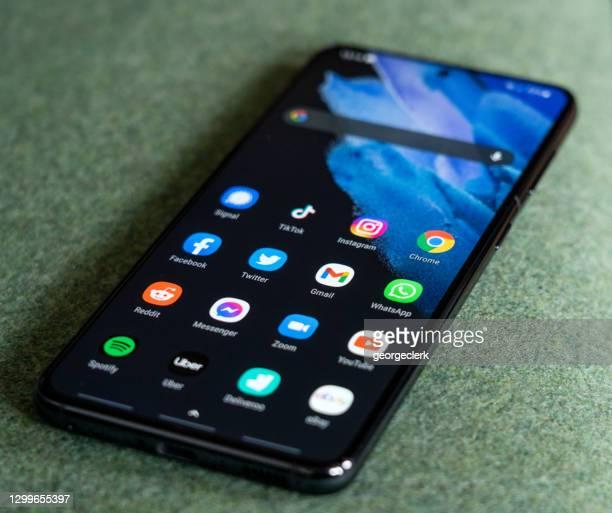 aplicaciones instaladas en un teléfono inteligente samsung galaxy s21 - google marca comercial fotografías e imágenes de stock