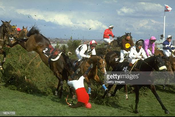 Jockey in red silk shirt falls off Ashley House after jumping The Chair during the Grand National at Aintree racecourse in Liverpool England...