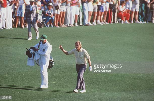 Jack Nicklaus signals to the galery as he walks up the 18th fairway with his caddy and son Jack Nicklaus Jr following his approach shot to the green...