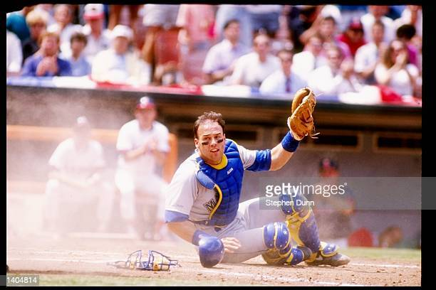 Catcher Dave Valle of the Seattle Mariners sits on the ground with his glove raised in the air during a game against the California Angels at Anaheim...