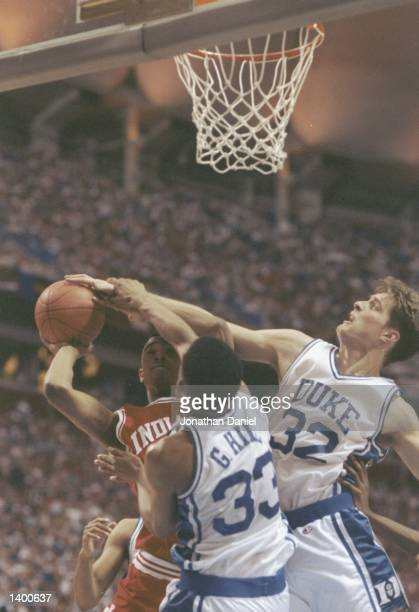 Alan Henderson of the Indiana Hoosiers tries to shoot the ball over center Christian Laettner and forward Grant Hill of the Duke Blue Devils during a...