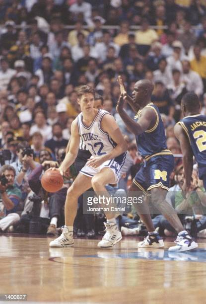 Ray Jackson of the Michigan Wolverines tries to guard center Christian Laettner of the Duke Blue Devils during a playoff game at the Hubert H...