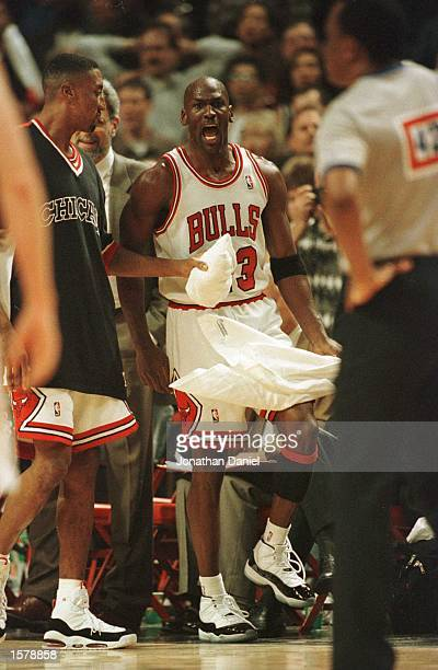 As teammate Scottie Pippen holds him back guard Michael Jordan of the Chicago Bulls has words for referee Hugh Hollins foreground who called a foul...
