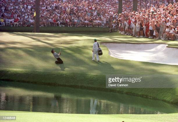 Greg Norman of Australia sinks to his knees on the 15th green after narrowly missing the hole with his chip shot during the final round of the 1996...