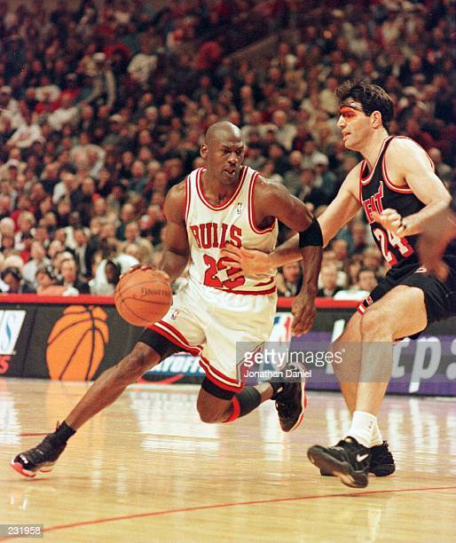 Guard Michael Jordan of the Chicago Bulls dribbles around the defensive pressure applied by Danny Schayes of the Miami Heat during the second quarter...