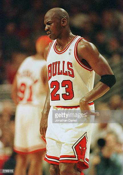 Michael Jordan of the Chicago Bulls winces in pain as he leaves the court after injuring his back during the second quarter of the their first round...