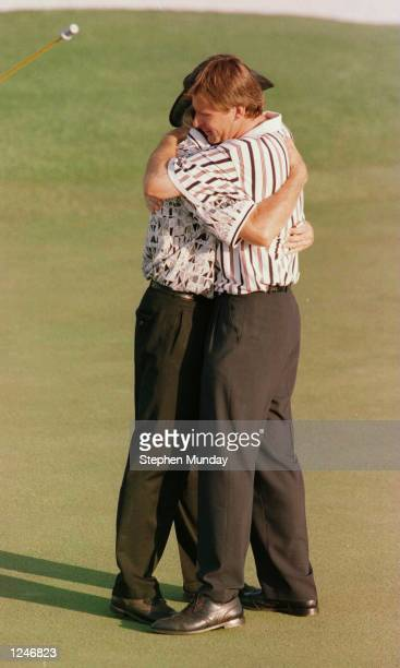 Nick Faldo of England hugs Greg Norman of Australia on the 18th green after winning the 1996 Masters during the final round of the 1996 Masters at...