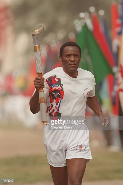 Olympic decathalete Rafer Johnson of the USA carries the Olympic torch on the first leg of the cross country relay from the Los Angeles Memorial...