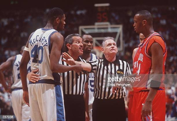 Referees try to defuse a confrontation between Walter McCarty of the Kentucky Wildcats and John Wallace of the Syracuse Orangemen during the final of...