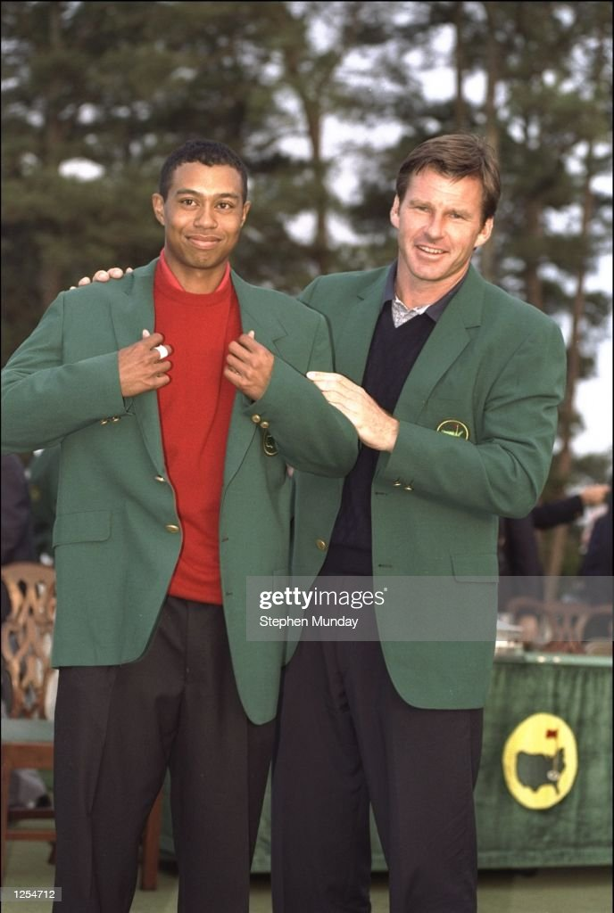 Masters winner Nick Faldo of Great Britain presents Tiger Woods of the USA with the winners green jacket after Woods won the 1997 US Masters tournament at Augusta with a record low score of 18 under par. \ Mandatory Credit: Stephen Munday /Allsport