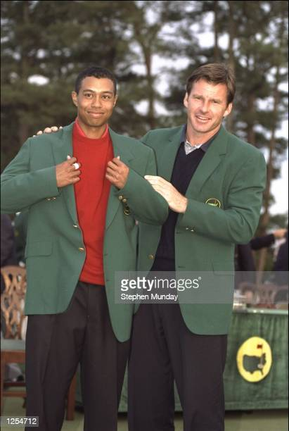 1996 US Masters winner Nick Faldo of Great Britain presents Tiger Woods of the USA with the winners green jacket after Woods won the 1997 US Masters...