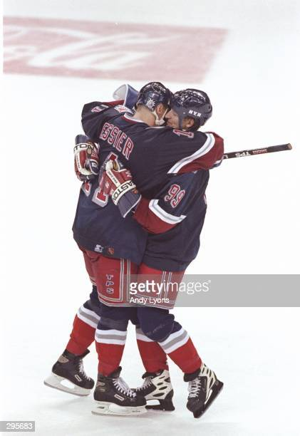 Centers Mark Messier and Wayne Gretzky of the New York Rangers hug each other during a playoff game against the Florida Panthers at the Miami Arena...
