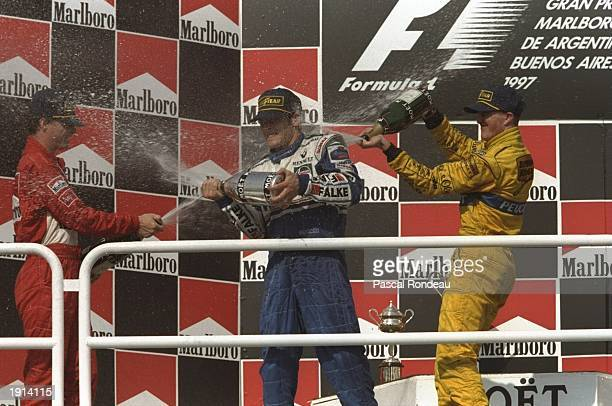 Eddie Irvine of Great Britain and Ralf Schumacher of Germany celebrate with Jacques Villeneuve of Canada during the Argentinian Grand Prix at Buenos...