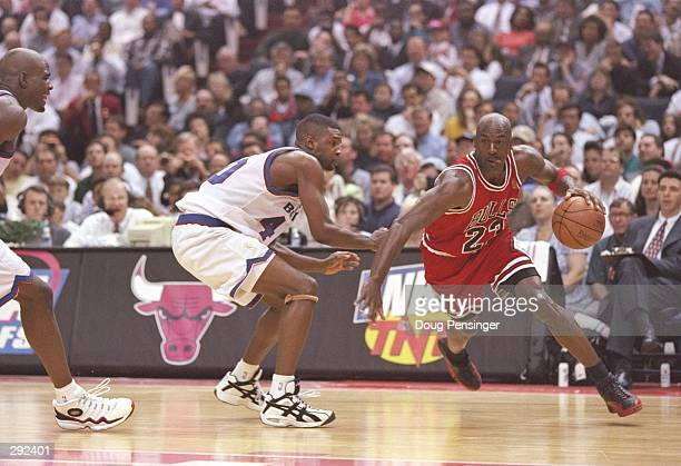 Guard Calbert Chaney of the Washington Bullets tries to guard guard Michael Jordan of the Chicago Bulls during a playoff game at the US Air Arena in...