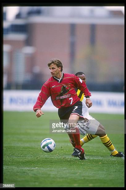 Mark Santel of the Dallas Burn runs down the field at Doctor Khumalo of the Columbus Crew chases him during a game at Ohio Stadium in Columbus Ohio...
