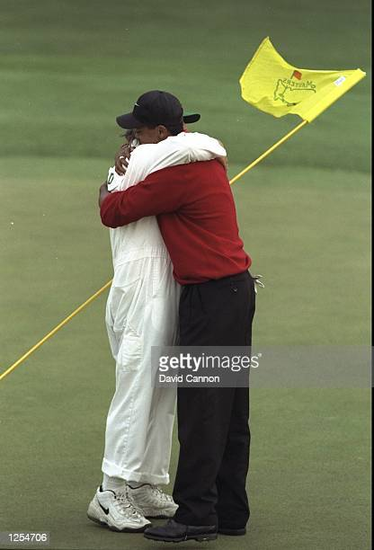 Tiger Woods of the USA embraces his caddie Mike 'Fluff' Cowan on the 18th green after winning the US Masters at Augusta Georgia Woods won the...