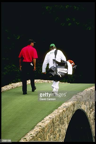 Tigers Woods walks with his caddie Mike Cowan across Hogan''s Bridge on the 12th hole at the Masters at the Augusta National Golf Course in Augusta...