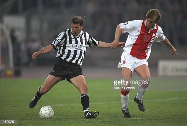 Zinedine Zidane of Juventus plays the ball closley watched marked by Richard Witchge of Ajax during the Champions League SemiFinal second leg at the...