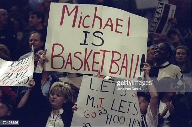 Fans of Michael Jordan of the Chicago Bulls hold up signs during a game against the New York Knicks at the United Center in Chicago, Illinois. The...