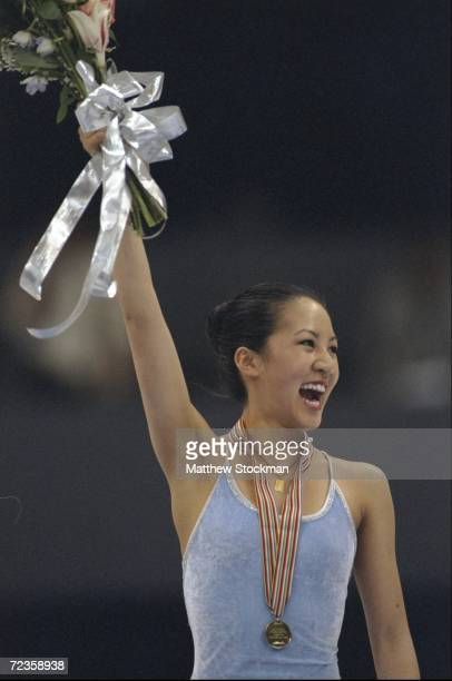 Michelle Kwan/USA holds up flowers as she celebrate after winning 1st place during the World Figure Skating Championships at Target Center Arena in...