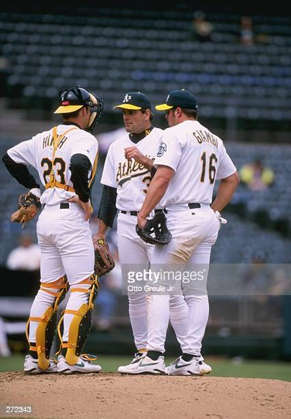 Pitcher Kenny Rogers, infielder Jason Giambi and catcher A.J. Hinch of the Oakland Athletics stand on the field during a game against the Boston Red...