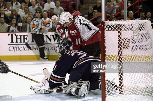 Right wing Keith Jones of the Colorado Avalanche and goaltender Curtis Joseph of the Edmonton Oilers in action during a playoff game at the McNichols...