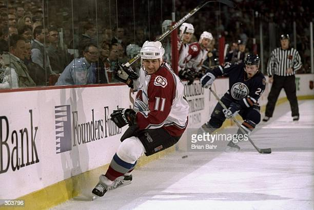 Right wing Keith Jones of the Colorado Avalanche and defenseman Janne Niinimaa of the Edmonton Oilers in action during a playoff game at the...
