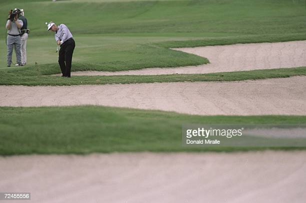 Bruce Fleisher chips his ball out of the sand trap as a tv camera watches him during the PGA Seniors Championships at the PGA National Golf Course in...