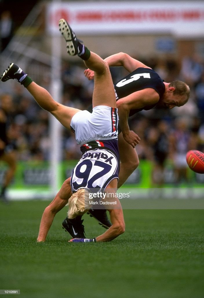 Clive Waterhouse (26) of Fremantle climbs over Andrew McKay (5) of Carlton during the 1999 AFL Premiership Round 4 game, where Carlton (121) defeated Fremantle (92), at the Optus Oval, Melbourne, Australia. \ Mandatory Credit: Mark Dadswell/Allsport