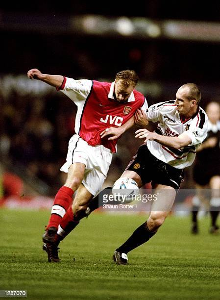 Dennis Bergkamp of Arsenal is closely watched by Jaap Stam of Manchester United in the FA Cup semifinal replay at Villa Park in Birmingham England...