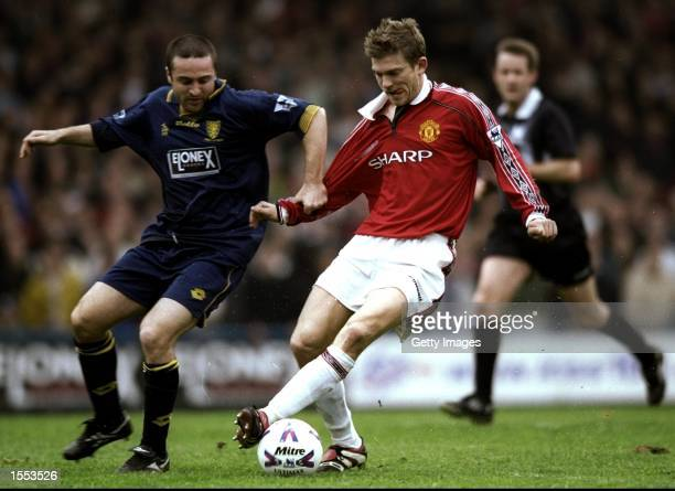 Jesper Blomqvist of Manchester United is challenged by Michael Hughes of Wimbledon during the FA Carling Premiership match played at Selhurst Park in...