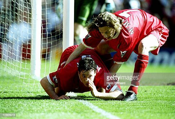 Robbie Fowler of Liverpool is pulled away by team mate Steve McManaman after mimicking cocaine snorting to celebrate his first goal against Everton...