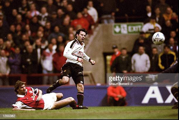 Ryan Giggs of Manchester United beats the despairing lunge of Tony Adams of Arsenal to drive the ball past David Seaman to score the winner in the FA...