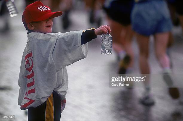 A youngster helps out at a water station during Flora London Marathon in London England Mandatory Credit Gary Palmer /Allsport
