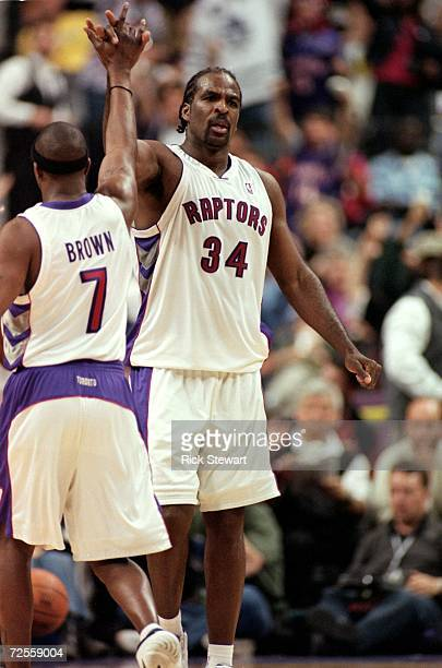 Charles Oakley of the Toronto Raptors gets high fived by Dee Brown during the NBA Eastern Conference Playoffs Round One Game against the New York...