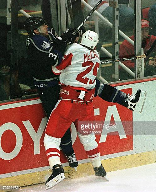 Garry Galley of the Los Angeles Kings is checked into the boards by Darren McCarty of the Detroit Red Wings during their opening round Western...