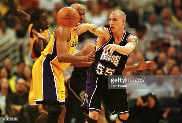 Guard Jason Williams of the Sacramento Kings passes around guard Ron Harper of the Los Angeles Lakers during game one of the NBA Playoffs at Staples...