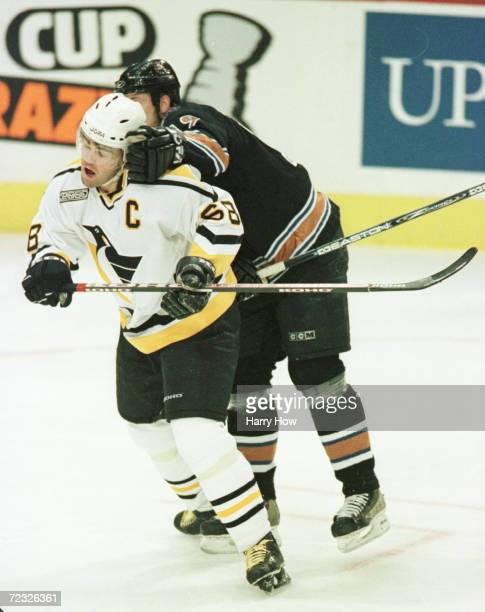 Jaromir Jagr of the Pittsburgh Penguins attempts to get away from the hands of Brendan Witt of the Washington Capitals at the Mellon Arena in...