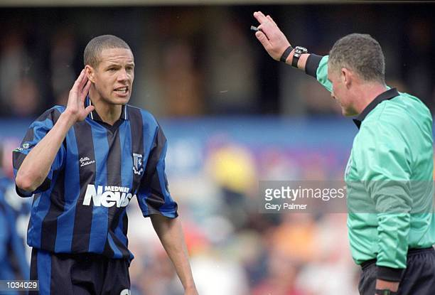 Junior Lewis of Gillingham is spoken to by referee Paul Rejer during the Nationwide League Division Two match against Millwall at the New Den in...