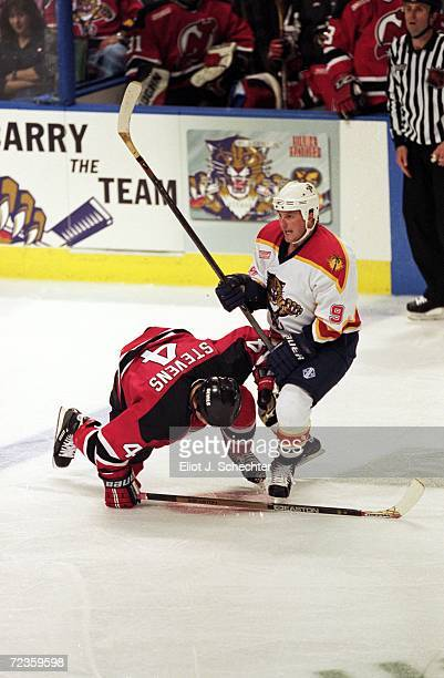 Len Barrie of the Florida Panthers knocks down Scott Stevens during the game against the New Jersey Devils at the National Car Rental Center in...