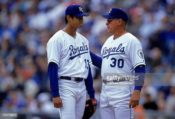 Mac Suzuki of the Kansas City Royals listens to Brent Strom during the game against the Minnesota Twins at Kauffman Stadium in Kansas City Missouri...